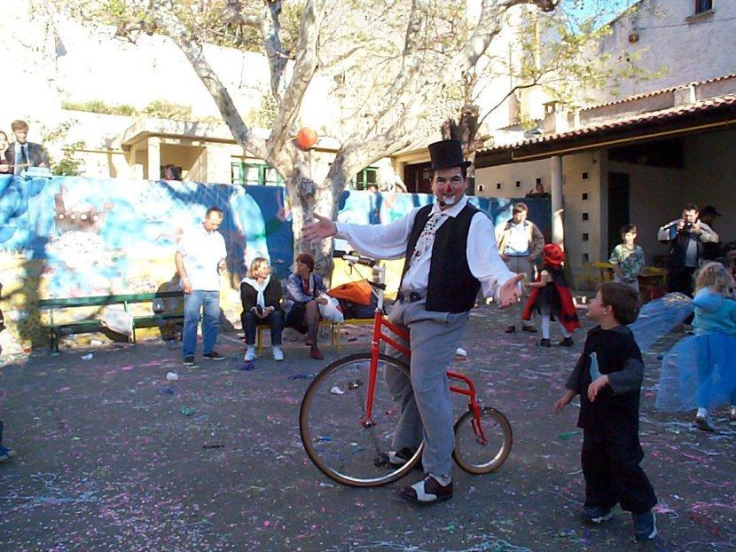 Clown sur son vélo grand Bi avec chapeau haut de forme en spectacle dans une école à Marseille Fabrizio le magicien, clown pour les écoles à Marseille